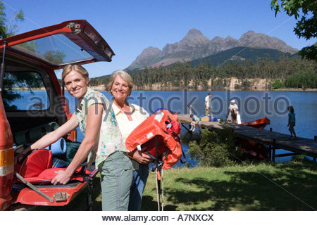 Multi generational family standing on lake jetty beside boat senior woman and adult daughter unloading life jackets - Stock Photo