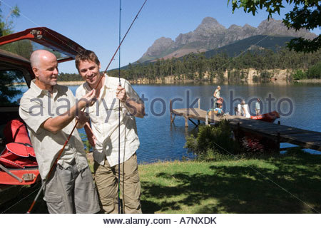 Senior man and adult son unloading fishing rods from SUV rest of family standing on lake jetty beside boat - Stock Photo