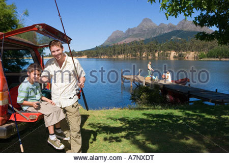 Father and son 8 10 with fishing rod beside SUV smiling portrait rest of family standing on lake jetty near boat - Stock Photo