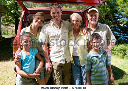 Multi generational family standing beside parked SUV smiling portrait - Stock Photo