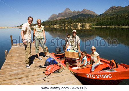 Multi generational family loading motorboat with provisions on lake jetty smiling portrait - Stock Photo
