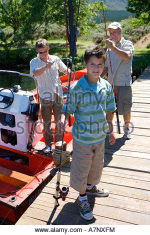 Boy 8 10 standing on lake jetty with fishing rod father and grandfather loading motorboat in background - Stock Photo