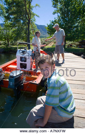 Boy 8 10 sitting on lake jetty smiling side view portrait father and grandfather loading fishing rods into motorboat - Stock Photo