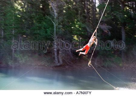 Boy 9 11 in swimming shorts swinging on rope above lake - Stock Photo