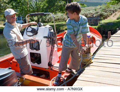 Grandfather and grandson 8 10 standing in motorboat beside lake jetty boy tying rope to mooring post - Stock Photo