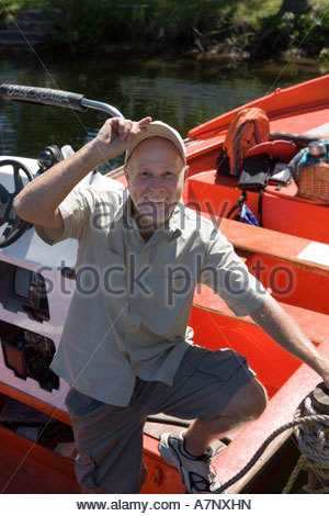 Senior man standing in motorboat beside lake jetty tilting cap smiling portrait - Stock Photo