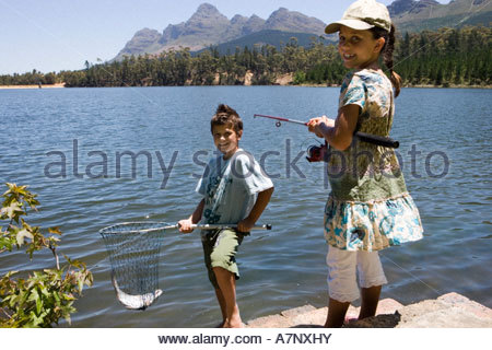 Brother and sister 7 10 fishing in lake boy holding fish in net girl holding rod smiling portrait - Stock Photo