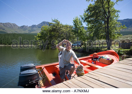 Senior man standing in moored motorboat beside lake jetty tilting cap admiring scenery smiling - Stock Photo