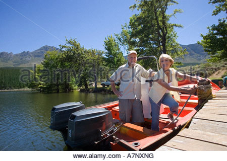 Senior couple standing in motorboat beside lake jetty woman tying rope to mooring post smiling portrait - Stock Photo