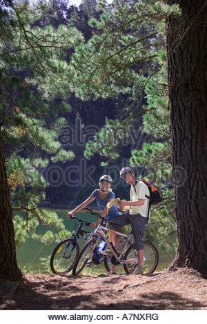 Young couple with rucksacks mountain biking along woodland trail beside lake holding map smiling portrait - Stock Photo