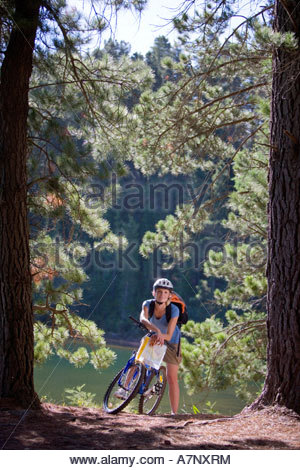 Woman with rucksack mountain biking along woodland trail beside lake holding map smiling portrait - Stock Photo