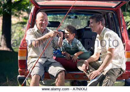 Boy 8 10 sitting in boot of parked SUV with father and grandfather senior man holding fishing rod smiling - Stock Photo