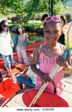 Family standing in motorboat focus on girl 7 9 standing on lake jetty holding fishing net smiling portrait - Stock Photo