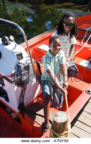 Father and son 8 10 standing in motorboat beside lake jetty boy tying rope to mooring post smiling portrait - Stock Photo