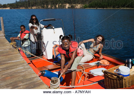 Family standing in motorboat beside lake jetty girl 7 9 tying rope to mooring post smiling portrait - Stock Photo