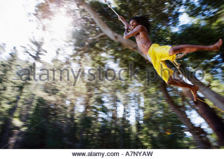 Boy 8 10 in yellow swimming shorts swinging on rope above lake low angle view backlit - Stock Photo