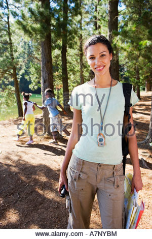Family hiking on woodland trail focus on woman in foreground smiling portrait - Stock Photo
