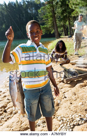 Family cooking food on camping trip beside lake boy 8 10 holding aloft fish in foreground smiling portrait - Stock Photo