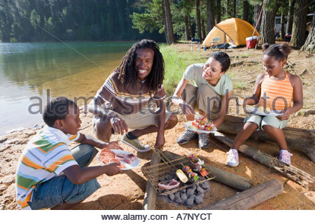 Family cooking food on camping trip beside lake smiling portrait - Stock Photo