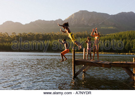 Family in swimwear standing on jetty father and son 8 10 jumping into lake side view - Stock Photo