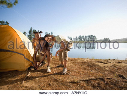 Family crouching beside tent on lakeside camping trip smiling portrait - Stock Photo