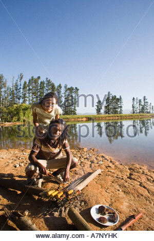 Couple cooking food on lakeside camping trip man grilling corncobs on campfire smiling portrait - Stock Photo