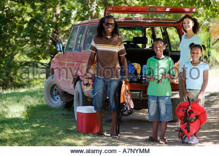 Family unloading parked SUV on camping trip girl 7 9 holding life jacket smiling portrait - Stock Photo