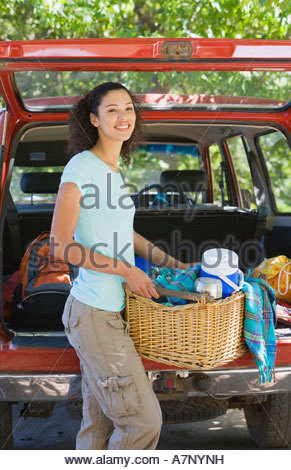 Woman unloading parked SUV on family camping trip carrying picnic hamper smiling portrait - Stock Photo