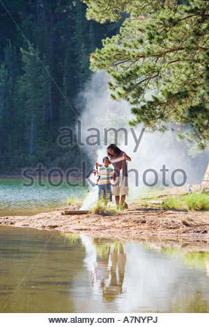 Father and son 8 10 in mid distance fishing near lakeside campfire man holding catch boy with fishing rod - Stock Photo