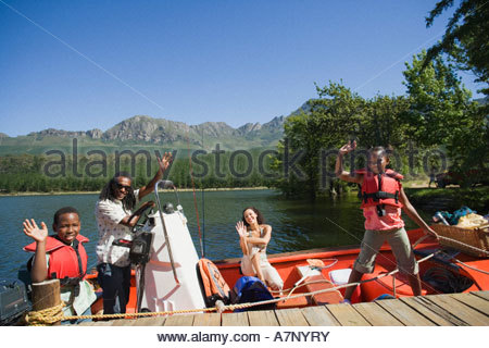Family departing on boating trip standing in motorboat beside lake jetty waving smiling side view portrait - Stock Photo
