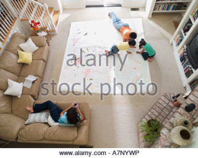 Family drawing on large piece of paper laid out on living room floor overhead view - Stock Photo