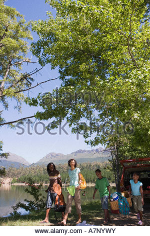 Family unloading provisions from parked SUV on lakeside camping trip smiling - Stock Photo