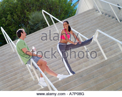 Couple in sportswear warming down from jog man leaning against railing on steps woman stretching leg tilt - Stock Photo