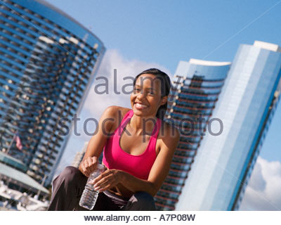 Woman in pink sports bra sitting on bench taking break from jogging in park holding water bottle smiling portrait - Stock Photo
