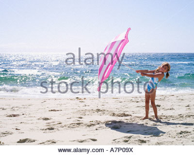 Girl (7-9), in swimsuit, playing with pink parasol on sandy beach near water's edge, smiling, side view, portrait - Stock Photo