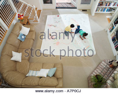 Boy and girl 7 10 drawing on large piece of paper laid out on living room floor overhead view - Stock Photo
