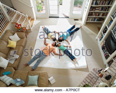 Family lying together on large piece of paper laid out on living room floor overhead view - Stock Photo
