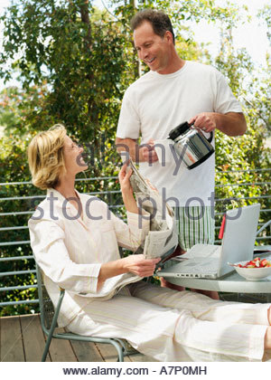 Couple relaxing on balcony man pouring cup of coffee woman sitting at table with newspaper and laptop - Stock Photo