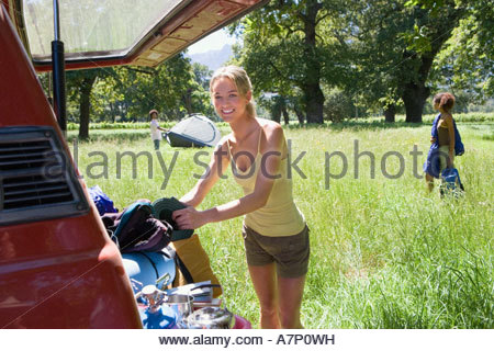 Young woman unloading parked SUV in woodland clearing on camping trip side view smiling portrait - Stock Photo