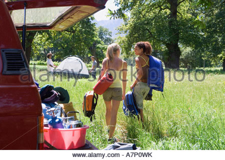 Two young women unloading parked SUV in woodland clearing on camping trip rear view smiling - Stock Photo