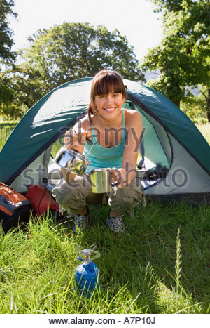 Young woman crouching beside dome tent in woodland clearing taking boiled kettle from camping stove smiling portrait - Stock Photo