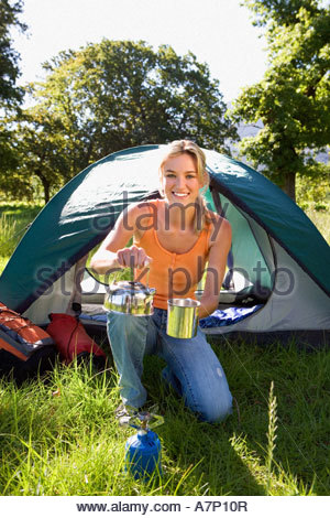 Young woman kneeling beside dome tent in woodland clearing taking boiled kettle from camping stove smiling portrait - Stock Photo