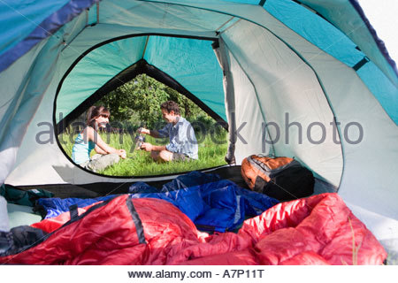 Tent interior view of couple sitting outside on grass pouring water from hot kettle - Stock Photo
