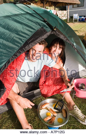 Couple sitting inside dome tent man cooking fried breakfast on camping stove smiling portrait tilt - Stock Photo