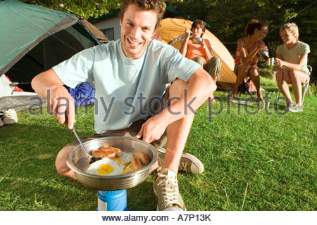 Young adults eating fried breakfast beside tents focus on man with spatula cooking on camping stove portrait tilt - Stock Photo