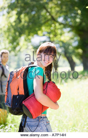 Young couple with rucksacks standing in woodland clearing departing on hiking trip woman carrying sleeping bag smiling - Stock Photo