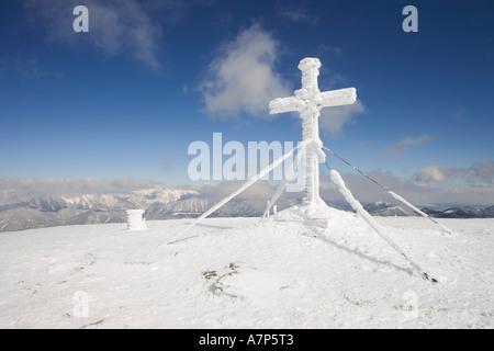 Snow covered cross on top of the mountain Stuhleck Styria Austria - Stock Photo