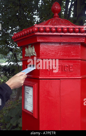 Person posting letter in a Victorian postbox. - Stock Photo