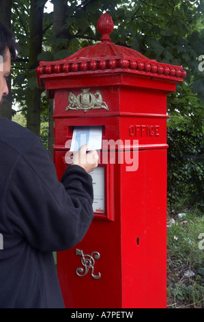 Man posting a letter in Victorian post box. - Stock Photo