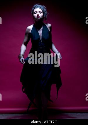 20 s female dancing in long black dress - Stock Photo